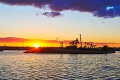 L'huile suçant la machine et le coucher du soleil de lac Photos libres de droits