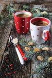 L'humeur de nouvelle année : deux tasses de branches de café et de pin Photographie stock libre de droits