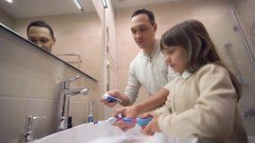 L'hygiène de matin d'enfants, jeune père enseigne la fille à brosser des dents et surveille la santé orale devant le miroir ci-de banque de vidéos