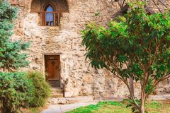 L'iarda del monastero antico con gli alberi e una porta in una parete fotografia stock libera da diritti