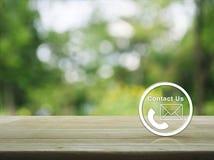 L'icône de téléphone et de courrier se boutonnent sur la table en bois au-dessus de l'arbre de tache floue Image stock