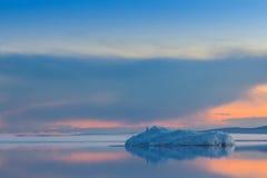 L'iceberg de fonte sur le lac de montagne de ressort dans le coucher de soleil Image stock