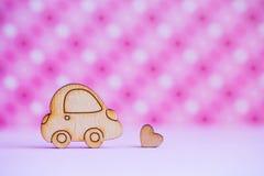 L'icona di legno dell'automobile con poco cuore sul rosa ha macchiato il fondo Immagine Stock Libera da Diritti