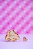 L'icona di legno dell'automobile con poco cuore sul rosa ha macchiato il fondo Immagini Stock Libere da Diritti