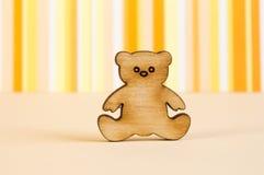 L'icona di legno dell'orsacchiotto riguarda il fondo a strisce arancio Immagine Stock Libera da Diritti