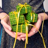 L'idée d'un concept minimal, une fille dans une belle robe juge beaucoup de de petits cadeaux, mains et cadeaux en gros plan photographie stock libre de droits