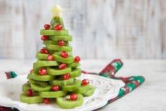 L'idea sana del dessert per i bambini fa festa - l'albero di Natale commestibile divertente del melograno del kiwi immagini stock