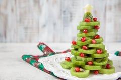 L'idea sana del dessert per i bambini fa festa - l'albero di Natale commestibile divertente del melograno del kiwi immagini stock libere da diritti