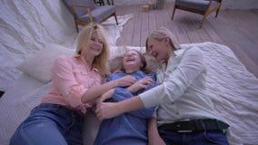 L'idillio della famiglia, mamma con le figlie cade sul letto ed insieme si diverte a casa stock footage