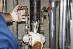 L'idraulico ripara i tubi nell'unità dell'impianto idraulico Mani che scandagliano con le chiavi su fondo dei tubi, dei manometri fotografie stock