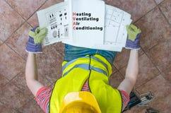 L'idraulico sta esaminando la documentazione della HVAC immagine stock