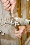 L'idraulico stringe la valvola Immagini Stock Libere da Diritti