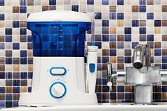 L'igiene orale, bagno obietta il concetto Dica i denti che puliscono lo strumento moderno di irrigator sul lavandino Fotografia Stock