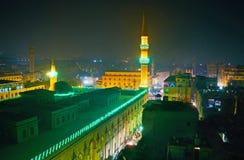L'illuminazione luminosa del minareto e delle pareti di Al-Hussain Mosque, circondati dai quarti scuri di uguagliare il distretto fotografia stock