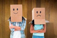 L'image composée de jeunes couples portant le visage triste enferme dans une boîte des frais généraux Image stock