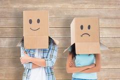 L'image composée de jeunes couples portant le visage triste enferme dans une boîte des frais généraux Photographie stock libre de droits