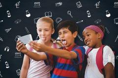 L'image composée de l'école badine prendre le selfie dans le couloir d'école Photos stock