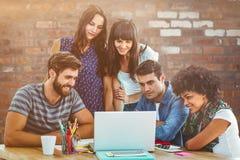 L'image composée de l'équipe créative heureuse d'affaires a recueilli autour d'un ordinateur portable photographie stock