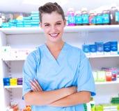 L'image composée de l'infirmière de sourire dans le bleu frotte posant avec des bras croisé Photographie stock