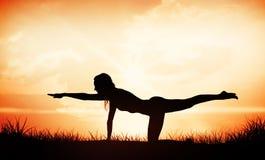 L'image composée de la blonde magnifique d'ajustement dans les pilates posent sur la plage photo libre de droits