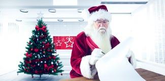 L'image composée de Santa écrit quelque chose avec une plume Photos stock