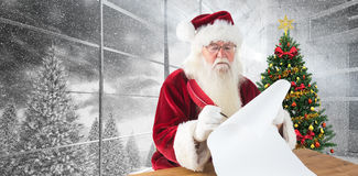 L'image composée de Santa écrit quelque chose avec une plume Images stock