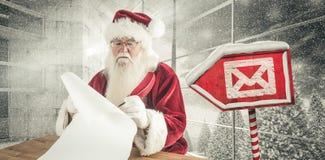 L'image composée de Santa écrit quelque chose avec une plume Image stock