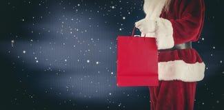 L'image composée de Santa porte le sac rouge de cadeau Photo libre de droits