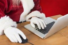 L'image composée de Santa surfe sur l'Internet Photos libres de droits