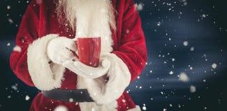 L'image composée de Santa tient une tasse rouge Photos stock