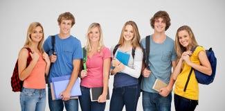 L'image composée des étudiants de sourire utilisant des sacs à dos et se tenant réserve dans leurs mains Image stock