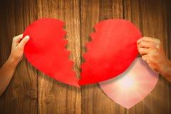 L'image composée des couples cultivés remet tenir la forme criquée rouge de coeur Photos stock