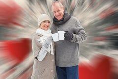 L'image composée des couples mûrs heureux en hiver vêtx tenir des tasses Photo libre de droits