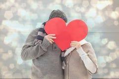 L'image composée des couples mûrs heureux en hiver vêtx tenir le coeur rouge Photographie stock libre de droits