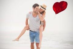 L'image composée des couples sur la plage et le coeur rouge montent en ballon 3d Images stock