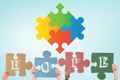L'image composée des mains supportant le puzzle d'espoir rapièce Photographie stock libre de droits