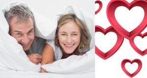 L'image composée du milieu heureux a vieilli des couples sous la couette Image libre de droits
