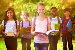 L'image composée du sourire peu d'école badine dans le couloir d'école Photographie stock libre de droits