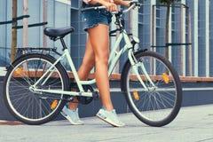 L'image cultivée d'une fille mince avec de longues jambes douces, denim de port court-circuite, se tenant avec le vélo de ville c Photos libres de droits