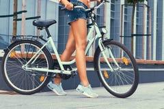 L'image cultivée d'une fille mince avec de longues jambes douces, denim de port court-circuite, se tenant avec le vélo de ville c Photo stock