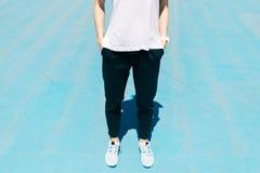 L'image cultivée d'une jeune femme dans des sports halète, T-shirt et Sn Image stock