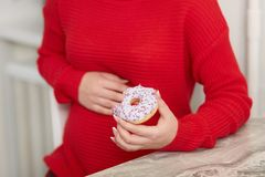L'image cultivée de la dame méconnaissable enceinte mange le beignet doux délicieux, garde la main sur le ventre, goûts nourritur image stock