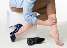 L'image cultivée de la femme dans des talons hauts la massant a fatigué des jambes Photos stock