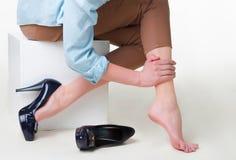 L'image cultivée de la femme dans des talons hauts la massant a fatigué des jambes Photos libres de droits