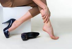 L'image cultivée de la femme dans des talons hauts la massant a fatigué des jambes Images libres de droits