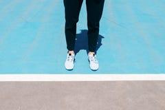 L'image cultivée des jambes femelles dans des espadrilles et le pantalon noir sont allumés Photographie stock libre de droits