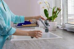 L'image cultivée des mains femelles avec une tasse verse l'eau du robinet filtrée dans la cuisine image libre de droits