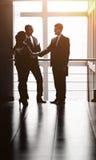 L'image d'une équipe d'affaires discutant les derniers bilans financiers et fixant l'affaire avec une poignée de main Image libre de droits