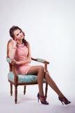 L'image de brune au printemps se repose sur une chaise dans le style baroque Photographie stock