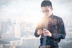 L'image de double exposition de l'homme d'affaires utilisant un smartphone pendant le lever de soleil recouvert avec l'image de p photo libre de droits